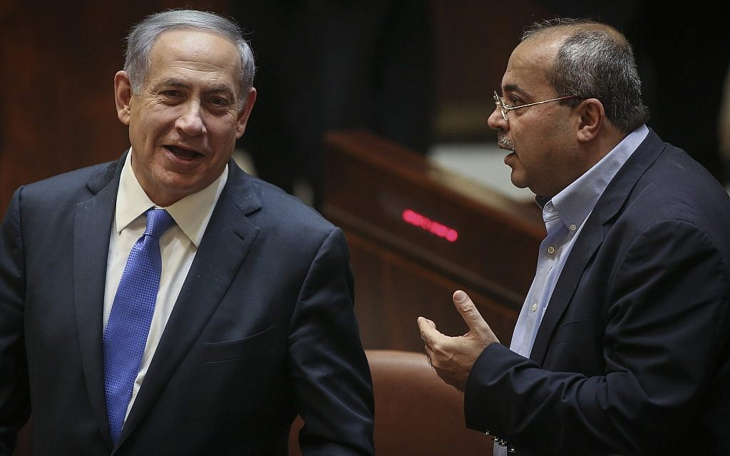 Prime Minister Benjamin Netanyahu (L) speaks with Joist (Arab) List MK Ahmad Tibi during a Knesset plenum session on June 29, 2015. (Hadas Parush/Flash90)