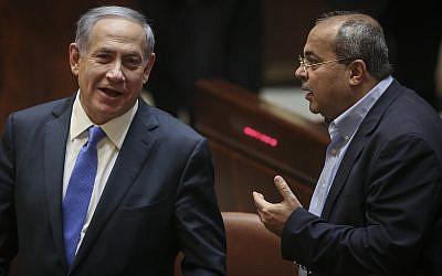 Prime Minister Benjamin Netanyahu (L) speaks with Joist (Arab) List MK Ahmad Tibi during a Knesset plenum session on June 29, 2015. (Hadas Parush/Flash90)