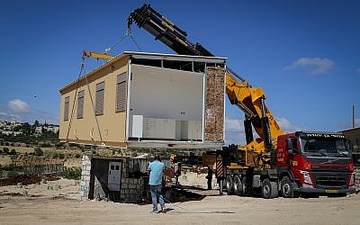 A crane lowers a caravan to the ground in a new settlement meant to resettle the evacuees of Netiv Ha'avot, in Gush Etzion, in the West Bank, May 9, 2018. (Gershon Elinson/Flash90)