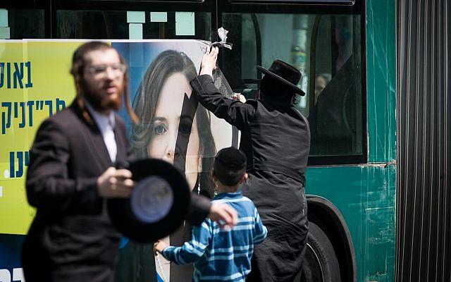 Ultra-Orthodox protesters vandalize an election poster of Jerusalem mayor candidate MK Rachel Azaria in Jerusalem's Mea Shearim neighborhood on July 26, 2018. (Yonatan Sindel/Flash90)