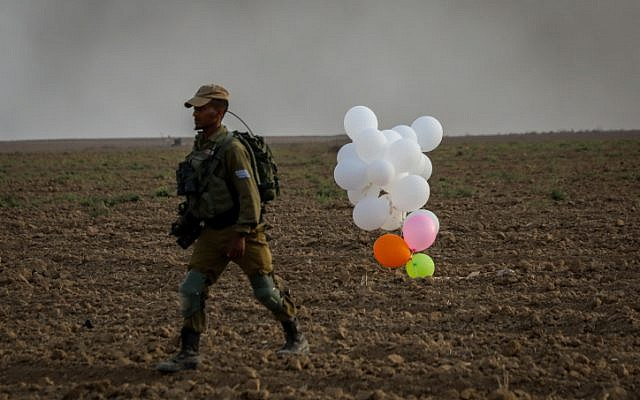 Illustrative: An Israeli soldier stands near balloons released by Palestinian protesters from the Gaza Strip that landed inside Israel on October 19, 2018. (Yossi Zamir/Flash90)