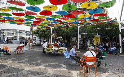 People sit outside the Carmel market in Tel Aviv, on October 22, 2018. (Sliman Khader/Flash90)