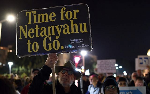 An Israeli man carries a sign citing conservative New York Times opinion columnist Bret Stephens as hundreds protest against Prime Minister Benjamin Netanyahu, Tel Aviv, March 02, 2019 (Gili Yaari/Flash90)