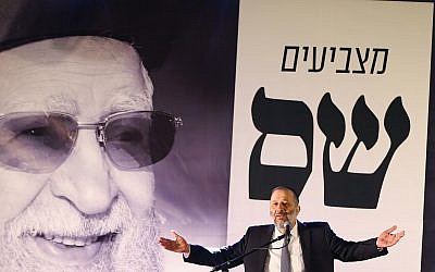 Aryeh Deri speaks in front of a picture of the late Rabbi Ovadia Yosef during a conference of the Shas party in the southern Israeli city of Ashdod on March 5, 2019. (Flash90)