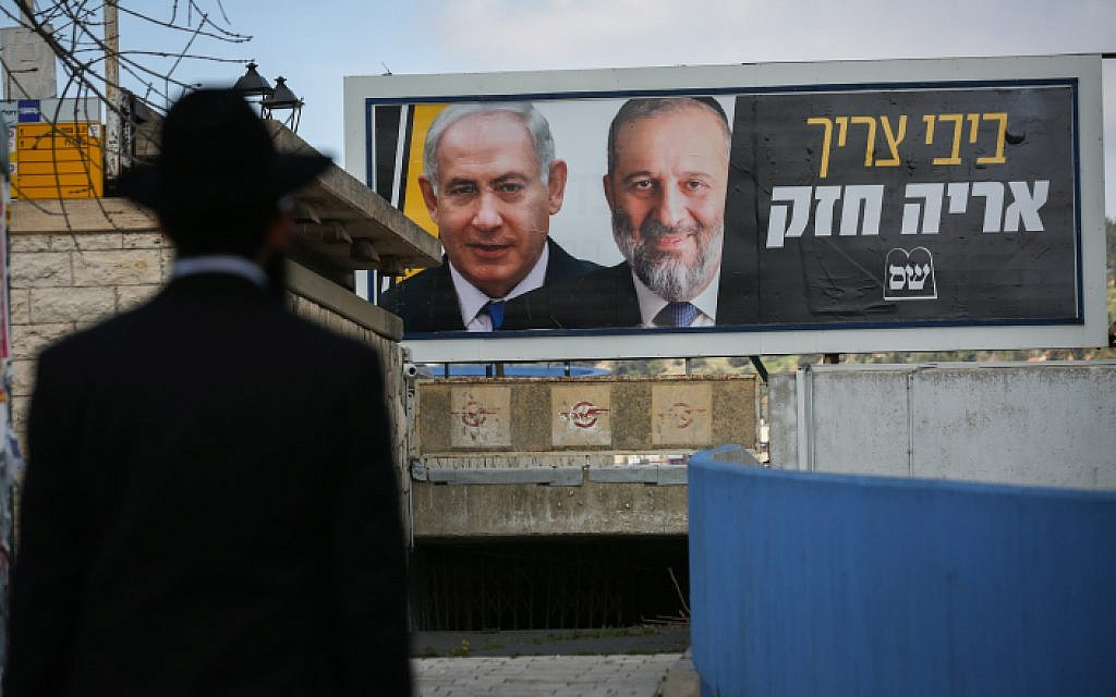 An ultra-Orthodox Jewish man near a billboard with pictures of Prime Minister Benjamin Netanyahu and Shas head Aryeh Deri, as part of the Shas election campaign, in Safed, March 10, 2019. (David Cohen/Flash90)