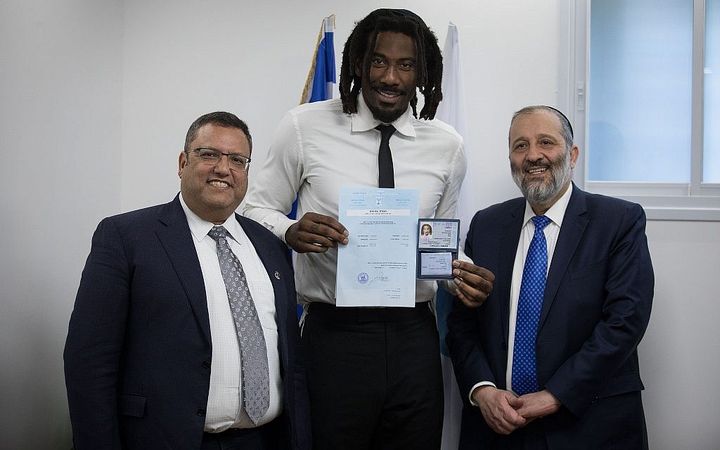 Basketball player Amar'e Stoudemire (C) shows off his Israeli national identity card at the Interior Ministry in Jerusalem alongside Interior Minister Aryeh Deri (R) and Jerusalem Mayor Moshe Lion on March 13, 2019. (Hadas Parush/Flash90)