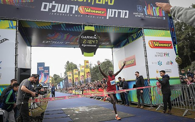 Ronald Kimeli, 33, from Kenya, crosses the finish line first at the 2019 international Jerusalem Marathon with a time of 02:18:47, on March 15, 2019. (Noam Revkin Fenton/Flash90)
