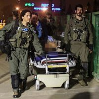 Israeli soldiers evacuate a wounded guard of the Israel Prison Service to Soroka Hospital in Beer Sheva, southern Israel, on March 24, 2019. Two prison service guards were stabbed by Hamas prisoners at the Ketziot Prison. (Meir Even Haim/Flash90 )