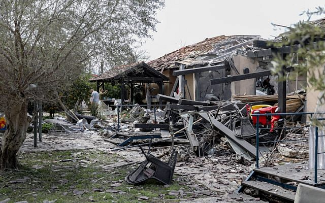 Israeli security forces inspect the scene of a house that was hit by a rocket fired from the Gaza Strip in the town of Mishmeret in central Israel on March 25, 2019. (Noam Revkin Fenton/Flash90)