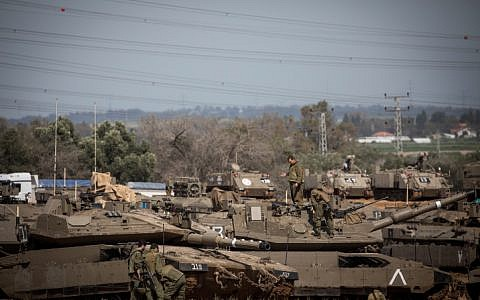 Israeli soldiers surround tanks stationed near the Israeli-Gaza border on March 26, 2018. (Yonatan Sindel/Flash90)