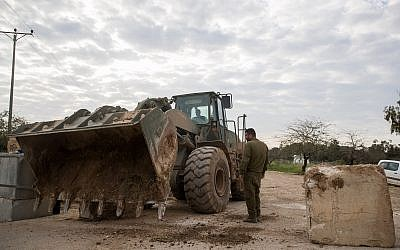 IDF soldiers stand by a military bulldozer moving concrete barricades to open a road that was shuttered by the army a day earlier near the Gaza border, on March 26, 2018. (Yonatan Sindel/Flash90)