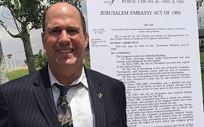 Farley Weiss, president of the National Council of Young Israel, poses next to the text of the Jerusalem Embassy Act of 1995. Weiss says political activism is part of Young Israel's mission. (Courtesy of Weiss/via JTA)