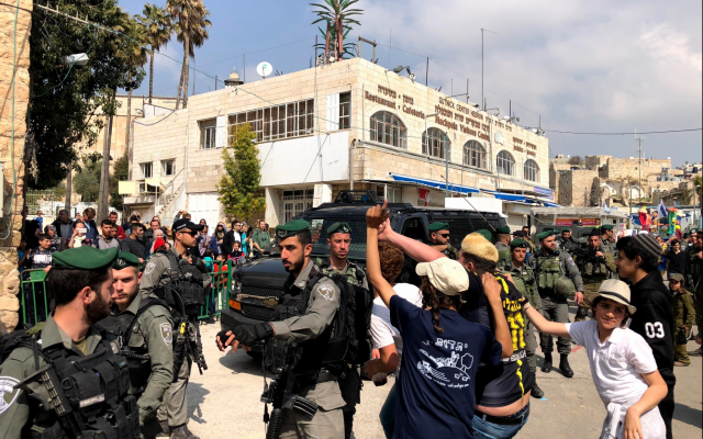 Israelis in Hebron parade through the streets in celebration of the Purim holiday on March 21, 2019. (Jacob Magid/Times of Israel)