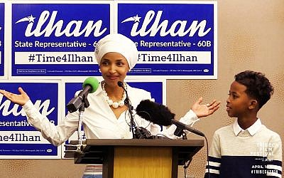 Then candidate for Minnesota Rep. Ilhan Omar campaigning in front of '#Time4Ilhan' posters. (Courtesy Norah Shapiro/ Chris Newberry)