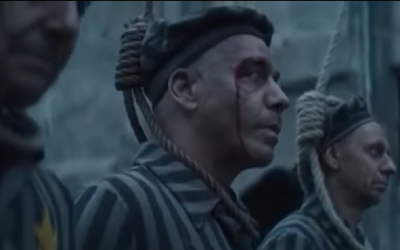 Members of German hard rock band Rammstein dressed as concentration camp inmates standing on a gallows, in a video for a new single released March 26, 2019 (YouTube screenshot)