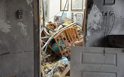 Police inspect a home in the central Israeli town of Mishmeret that was destroyed in a rocket attack from the Gaza Strip on March 25, 2019. (Israel Police)