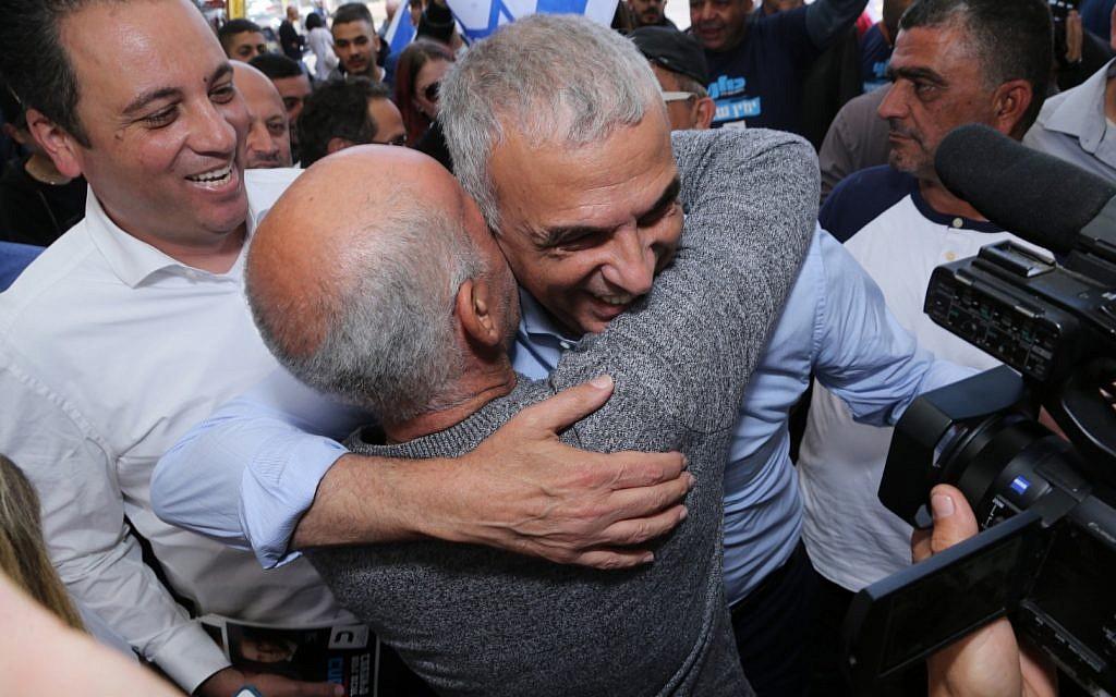 Kulanu leader Moshe Kahlon (R) embracing a supporter during a visit to Tel Aviv's Hatikva Market, March 28, 2019. (Kulanu)