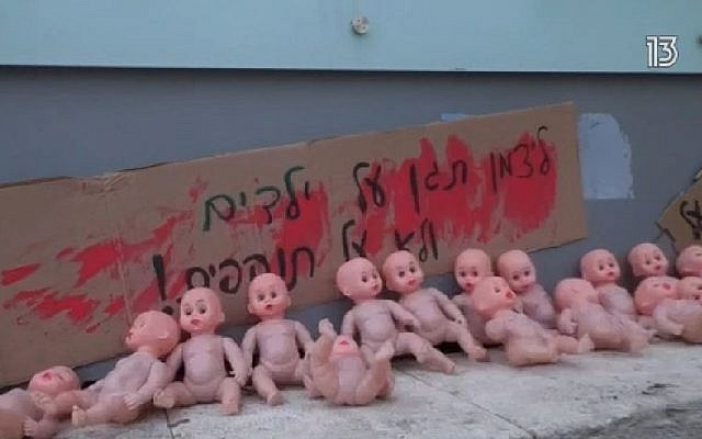"Baby-doll protest outside the Health Ministry's offices in Jerusalem over Deputy Health Minister Yaakov Litzman's alleged aid to suspected child sex abusers, March 4, 2019. The sign reads, ""Litzman, protect the children, not the abusers!"" (Channel 13 screen capture)"