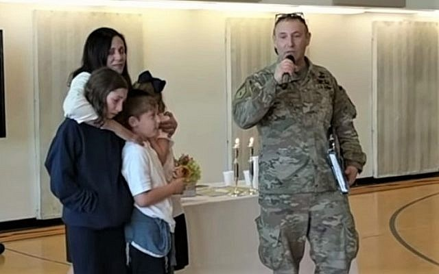 Major Moses Scheinfeld standing next to his family, addresses his children's school after he surprised them by returning from active duty in Afghanistan in time for Purim. (Screen capture from YouTube)