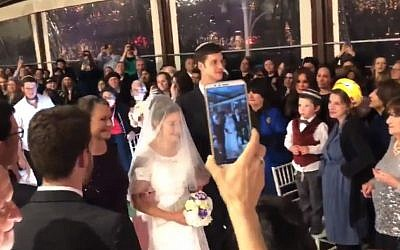 Tamar Fuld flanked by her mother, Miriam and brother Yakir, walks towards the huppah at her wedding on March 3, 2019. (Screen capture: Twitter)