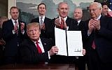 US President Donald Trump, seated, holds up a signed proclamation on the Golan Heights, alongside Israeli Prime Minister Benjamin Netanyahu, standing center, in the Diplomatic Reception Room at the White House in Washington, DC, March 25, 2019. (Saul Loeb/AFP)