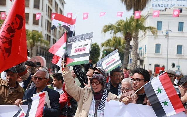 Tunisians hold Syrian and Palestinian flags, as they demonstrate against the Arab League Summit and the United States' recognition of Israeli sovereignty over the Golan Heights, on Habib Bourguiba Avenue, in the capital Tunis on March 31, 2019. (Anis Mili/AFP)