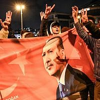 Supporters of Justice and Development party (AKP) wave a flag picturing Turkish president Recep Tayyip Erdogan as they celebrate during a post-election rally near the party's headquarters on March 31, 2019, in Istanbul. (Ozan KOSE / AFP)