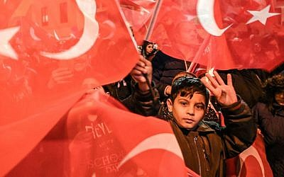 "A child flashes the four-finger ""Rabia sign"" among supporters of Justice and development party (AKP) wawing Turkish national and party flags during a rally near the headquarters of the conservative AKP party on March 31, 2019 in Istanbul.(Photo by Ozan KOSE / AFP)"