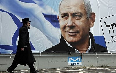 An ultra-Orthodox Jewish man walks past an electoral billboard bearing a portrait of Prime Minister Benjamin Netanyahu, in Jerusalem, on April 1, 2019. (Thomas Coex/AFP)
