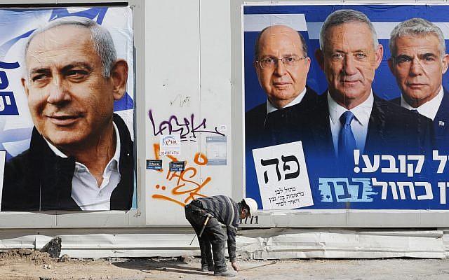 A laborer walks past electoral campaign posters in Tel Aviv, on April 3, 2019. ( JACK GUEZ / AFP)