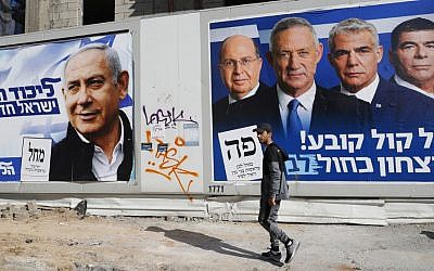 A man walks past campaign posters bearing the portraits of Prime Minister Benjamin Netanyahu (L) and former IDF chief of staff Benny Gantz (R), one of the leaders of the Blue and White party, in Tel Aviv on April 3, 2019. (Jack Guez/AFP)