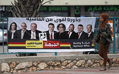 An Israeli Arab woman walks past a campaign poster showing Israeli-Arab candidates in Kafr Manda. (AHMAD GHARABLI / AFP)