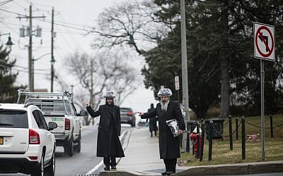 Illustrative: This picture taken on April 5, 2019 shows shows two Jewish men hitchhiking during a rainfall in a Jewish neighborhood of Monsey in Rockland County, New York. (Johannes Eisele/AFP)