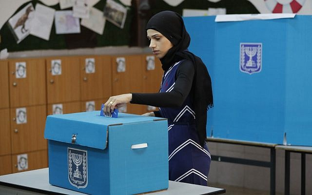 Illustrative: An Arab Israeli woman casts her vote during elections for the Knesset on April 9, 2019, at a polling station in the northern town of Tayibe. (Ahmad Gharabli/AFP)