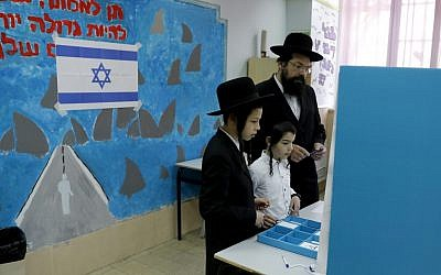 Children watch as an ultra-Orthodox Jewish man prepares to cast his vote during Israel's parliamentary elections on April 9, 2019 in Jerusalem. (Menahem Kahana/AFP)