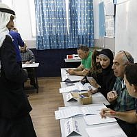 An Arab Israeli man (L) registers before voting in elections for the Knesset on April 9, 2019 at a school turned polling station in the northern town of Tayibe. (Ahmad Gharabli/AFP)