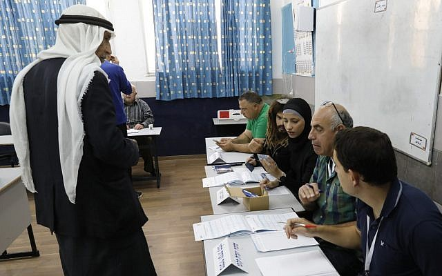 An Arab Israeli man (L) registers before voting in elections for the Knesset on April 9, 2019, at a school turned polling station in the northern town of Tayibe. (Ahmad Gharabli/AFP)