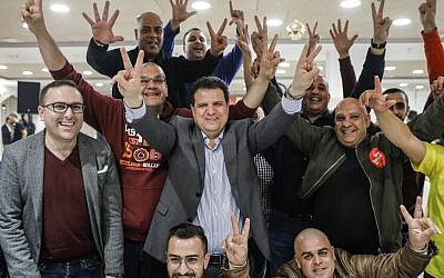 Israeli Arab politician Ayman Odeh (c) of the Hadash party flashes the victory gesture as he reacts at the party's headquarters in Nazareth in northern Israel on election tonight on April 9, 2019. (AFP/Ahmad Gharabli)