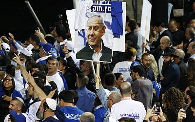 Supporters of Likud wave party and national flags along with a sign showing Prime Minister Benjamin Netanyahu as they gather at the party's headquarters in Tel Aviv on election night early on April 10, 2019.  (Jack GUEZ / AFP)