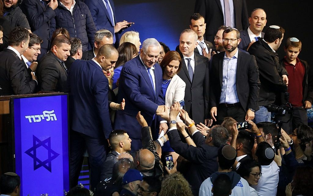 Israeli Prime Minister Benjamin Netanyahu (C) greets supporters at his Likud Party headquarters in the Israeli coastal city of Tel Aviv on election night early on April 10, 2019. (Photo by Jack GUEZ / AFP)