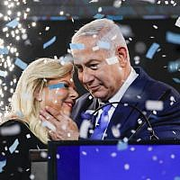 Prime Minister Benjamin Netanyahu embraces his wife Sara amid confetti during his victory speech before supporters at Likud party headquarters in Tel Aviv after April 9, 2019's elections. (Thomas Coex/AFP)