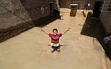 An Iranian child gestures for the camera at a flooded house in the city of Hamidiyeh, in Iran's Khuzestan province, on April 10, 2019.(ATTA KENARE / AFP)