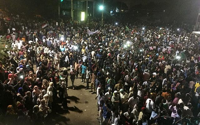Sudanese demonstrators chant slogans as they gather at night during a demonstration in front of the military headquarters in the capital Khartoum on April 10, 2019. (AFP)