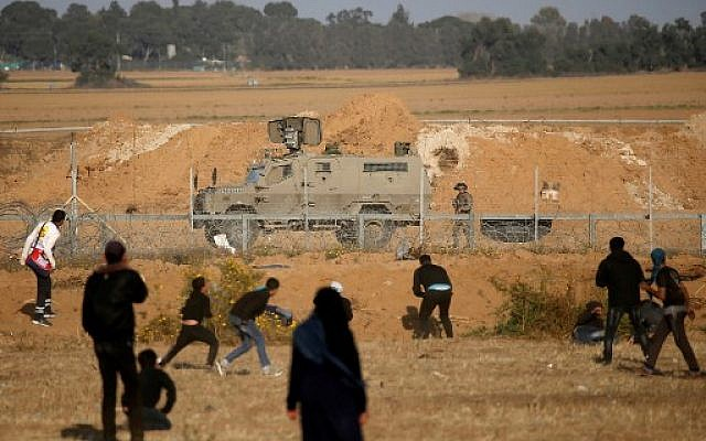 Illustrative: Palestinians confront Israeli forces near the border with Israel, east of Khan Younis in the southern Gaza Strip, on April 12, 2019. (Said Khatib/AFP)