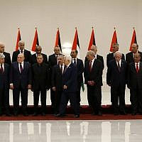 Palestinian Authority President Mahmoud Abbas (6th-right) walks away after posing for a group photograph with members of the new Palestinian Authority government in the West Bank city of Ramallah on April 13, 2019. (Abbas Momani/AFP)