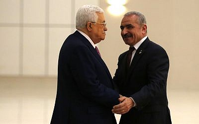 Palestinian Authority President Mahmoud Abbas (L) shakes hands with the prime minister-designate Mohammad Shtayyeh in the West Bank city of Ramallah, on April 13, 2019. (Abbas Momani/AFP)