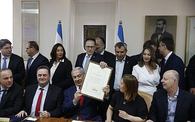 Israeli Prime Minister Benjamin Netanyahu (C) holds a proclamation signed by U.S. President Donald Trump recognizing Israel's sovereignty over the Golan Heights, during a weekly cabinet meeting in Jerusalem on April 14, 2019. (Photo by RONEN ZVULUN / AFP)