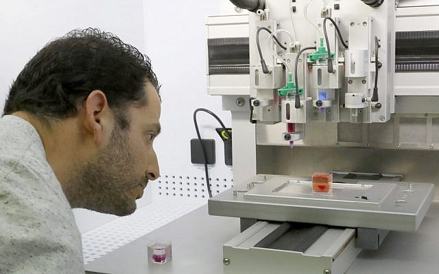 Dr. Assaf Shpira looks at a 3D print of heart with human tissue at the University of Tel Aviv