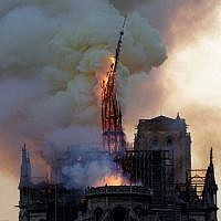 The spire of the landmark Notre Dame Cathedral collapses as the cathedral is engulfed in flames in central Paris on April 15, 2019. (Geoffroy VAN DER HASSELT / AFP)