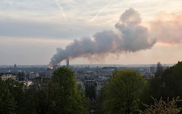 Seen from the Belleville Park, smoke and flames rise during a fire at the landmark Notre Dame Cathedral in central Paris on April 15, 2019. (Aurore MESENGE / AFP)